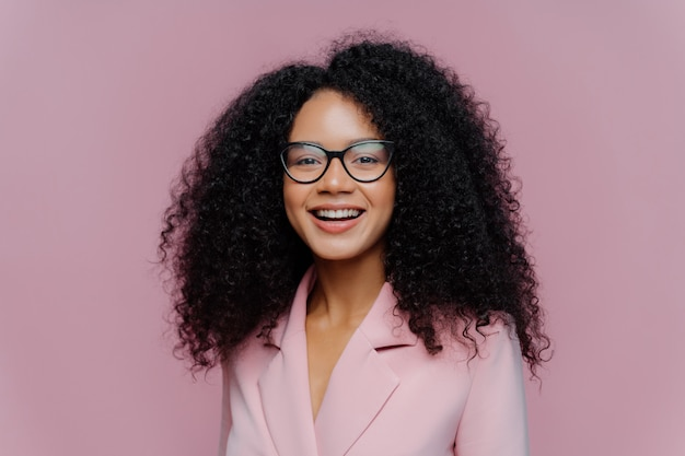 Sluit omhoog portret van gelukkige etnische jonge vrouw met kernachtig haar en kijkt door optische glazen