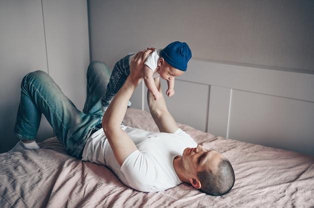 Sluit omhoog portret van gelukkige jonge papavader die zijn baby in jeans en witte t-shirt en glb houdt. jonge gelukkige familie, vader spelen met schattige emotionele kleine pasgeboren kind-zoon in de slaapkamer.