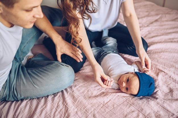 Sluit omhoog portret van gelukkige ouders die hun baby houden. jonge gelukkige familie, moeder en vader spelen met schattige emotionele kleine pasgeboren kind zoon in de slaapkamer