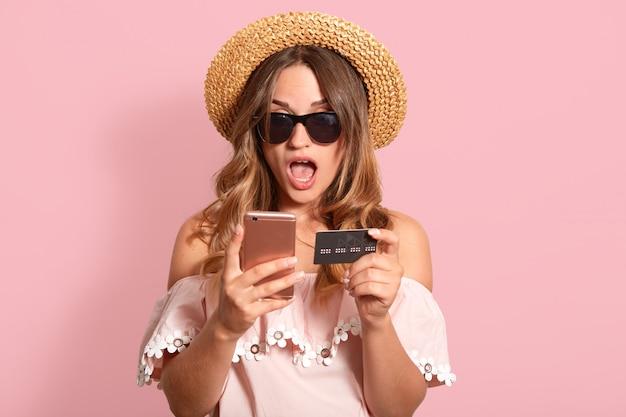 Sluit omhoog portret van geschokt emotioneel wijfje met wijd geopende mond, stellen geïsoleerd op roze in studio, houdend creditcard en smartphone in beide handen, doend aankopen.