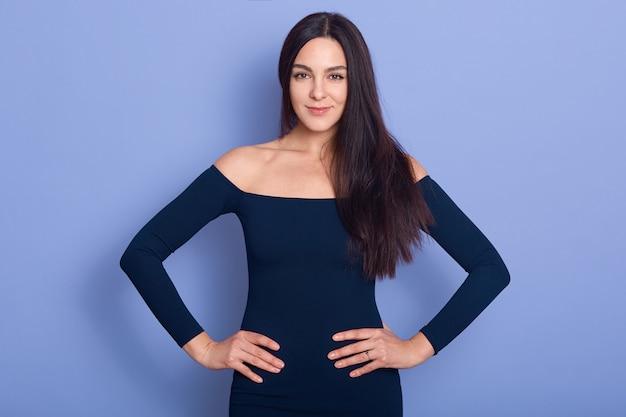 Sluit omhoog portret van glimlachende elegantievrouw die modieuze kleding dragen die zich met handen op heup bevinden en glimlachend camera bekijken, het aantrekkelijke meisje stellen met naakte schouders isoalted op blauw.