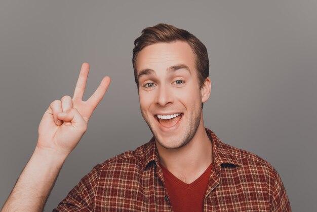 Sluit omhoog portret van glimlachende mens die twee vingers toont