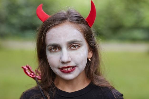 Sluit omhoog portret van glimlachende tienermeisje die duivelskostuum en schmink in openlucht dragen