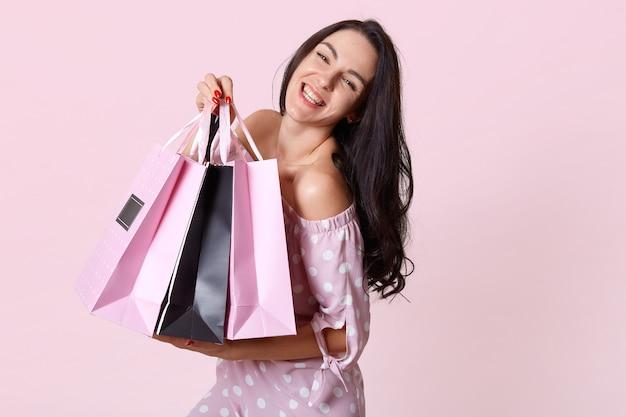 Sluit omhoog portret van glimlachende vrouw met lang donker haar, geklede stipkleding, het houden van boodschappentassen en tribunes glimlachend, uitdrukt happyness, geïsoleerd stellen op rooskleurig.