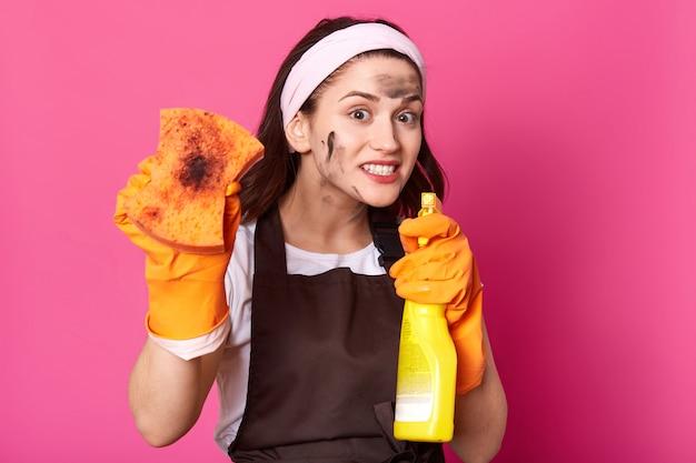 Sluit omhoog portret van grappig actief donkerbruin model wijst fles schoonmakend detergens bij camera, tonend vuile oranje spons, hebbend heldere heldere gelaatsuitdrukking, genietend van tijd van schoonmaak.