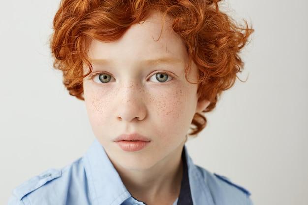 Sluit omhoog portret van grappig klein jong geitje met oranje haar en sproeten. jongen die met ontspannen en kalme gezichtsuitdrukking kijkt.