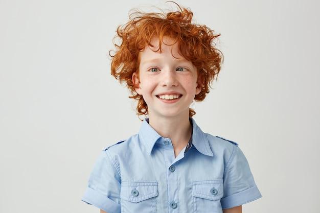 Sluit omhoog portret van grappig weinig jongen met oranje haar en sproeten die ogen maaien, en dwaze gezichten glimlachen maken