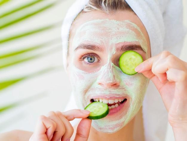 Sluit omhoog portret van grappige glimlachende vrouw die natuurlijk groen gezichtsmasker met plakjes komkommer toepast.