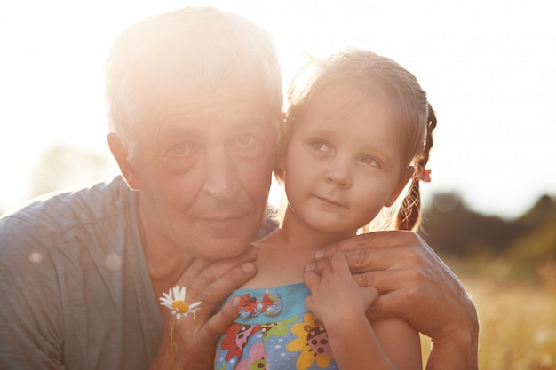 Sluit omhoog portret van grijze haired grootvader omhelst met liefde weinig kleindochter, heb waarheidsgetrouwe relaties