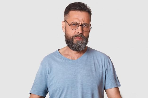 Sluit omhoog portret van het boze mens stellen in studio geïsoleerd over witte muur, kerel die bril en grijze toevallige t-shirt draagt, die baard heeft