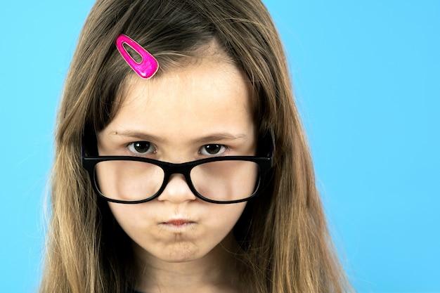 Sluit omhoog portret van het boze ontstemde meisje van de kindschool dragen kijkend glazen geïsoleerd op blauw