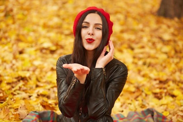 Sluit omhoog portret van het elegante vrij donkerbruine vrouw stellen bij de herfst heldere dag in stadspark, dragend elegante rode baret