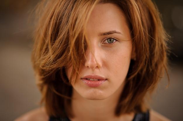 Sluit omhoog portret van het jonge en mooie gezicht van de roodharigevrouw