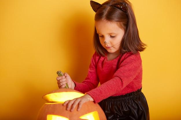 Sluit omhoog portret van het leuke meisje spelen met haar halloween-pompoen, jong geitje die sweater en zwarte rok dragen, weinig charmant model met kattenoren