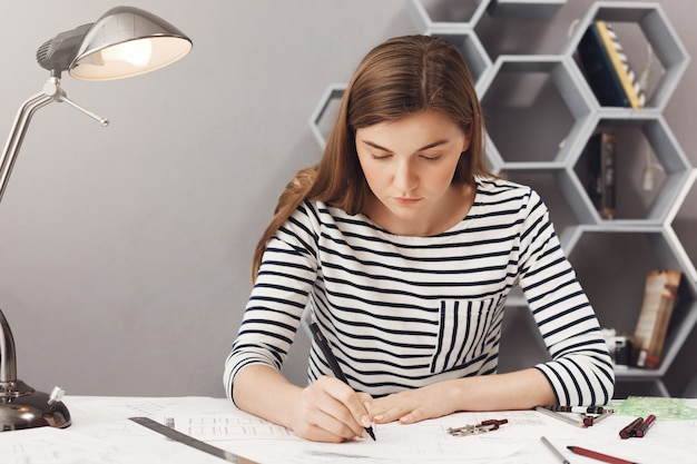 Sluit omhoog portret van jong ernstig architectenmeisje die haar werk in comfortabele coworkingruimte doen, bekijkend document met ernstige en ongelukkige uitdrukking.