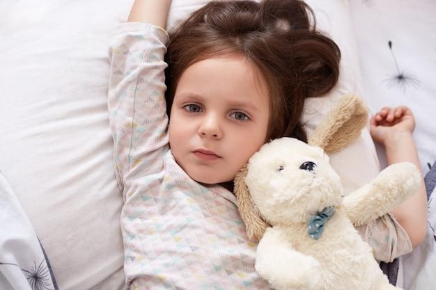 Sluit omhoog portret van jong geitje liggend bed met hond, legt op hoofdkussen, schattig kind dat pyjama draagt, kind dat met zacht stuk speelgoed speelt alvorens te gaan slapen