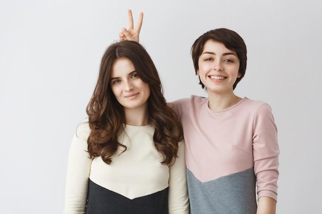 Sluit omhoog portret van jong gelukkig lesbisch paar met donker haar in passende kleren glimlachen, hebbend pret, stellend voor spruit in fotocabine.