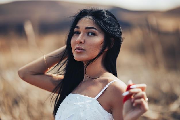 Sluit omhoog portret van jong sexy donkerbruin meisje in aard. kazachse jonge vrouw geniet lente ochtend en winter in haar haar, geselecteerde focus