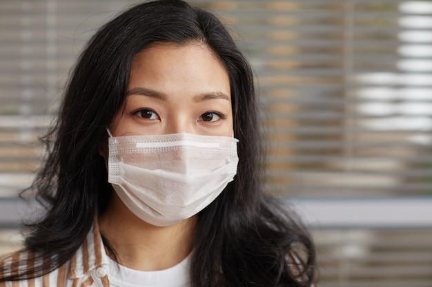 Sluit omhoog portret van jonge aziatische vrouw die masker draagt en camera tegen bureauzonneblindenachtergrond bekijkt, exemplaarruimte