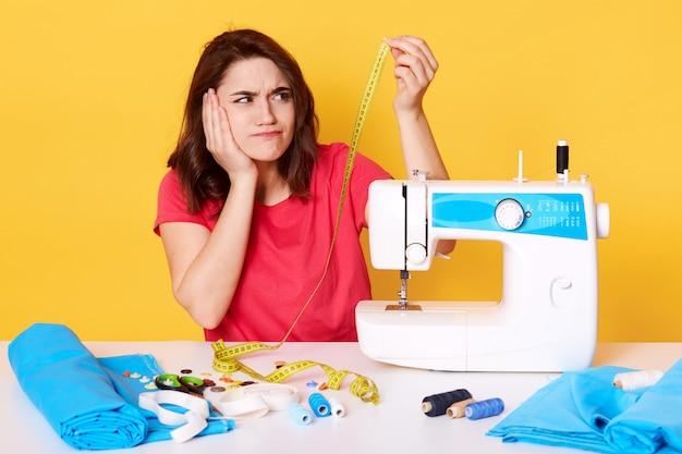 Sluit omhoog portret van jonge donkerbruine vrouw in toevallige rode t-shirtzitting dichtbij naaimachine