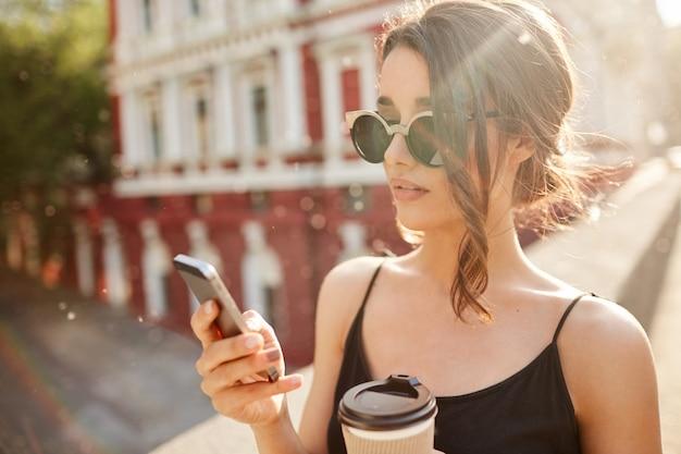 Sluit omhoog portret van jonge knappe ernstige spaanse vrouw die met vriend babbelen dat die laat voor vergadering op celtelefoon, koffie drinken, zonnige de zomerdag buiten doorbrengen.