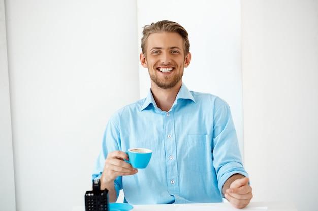 Sluit omhoog portret van jonge knappe vrolijke glimlachende zakenman die zich bij de koffiekop van de lijstholding bevinden. . witte moderne kantoor interieur