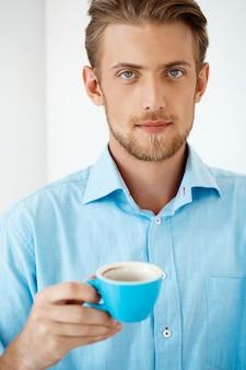 Sluit omhoog portret van jonge knappe zekere peinzende zakenman die zich bij de koffiekop van de lijstholding bevinden. . witte moderne kantoor interieur