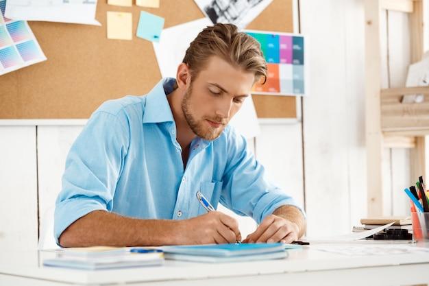 Sluit omhoog portret van jonge knappe zekere peinzende zakenman werkende zitting bij lijst schrijvend in notitieboekje. witte moderne kantoor interieur