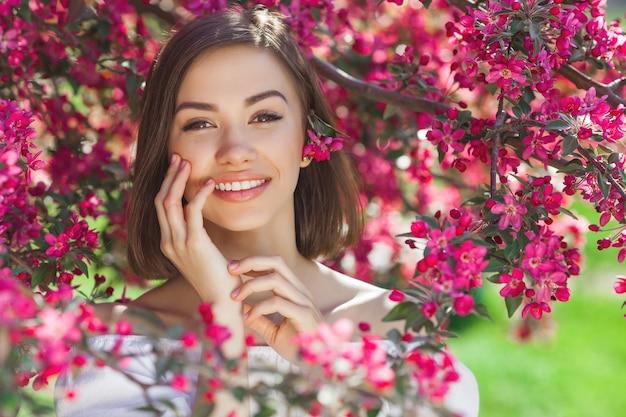 Sluit omhoog portret van jonge mooie vrouw met perfecte vlotte huid. aantrekkelijke dame in bloemen. gezichtsportret van mooi wijfje.