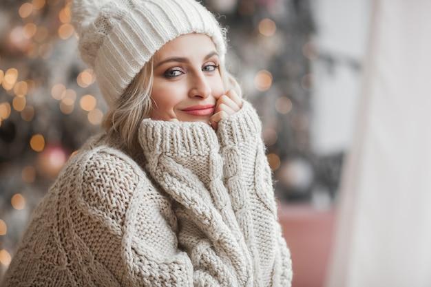 Sluit omhoog portret van jonge mooie vrouw op kerstmisscène. glimlachend meisje met perfecte huid dichtbij de kerstboom.