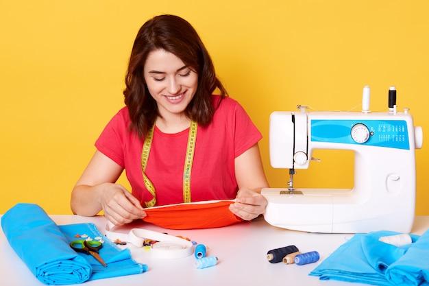 Sluit omhoog portret van jonge naaistervrouw naait kleren op naaimachine