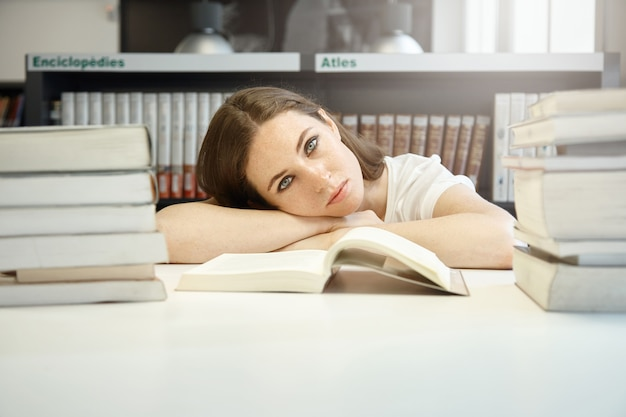 Sluit omhoog portret van jonge student bij bibliotheek voorbereidend op laatste examens, rustend haar hoofd op handen, droevig en vermoeid kijkend