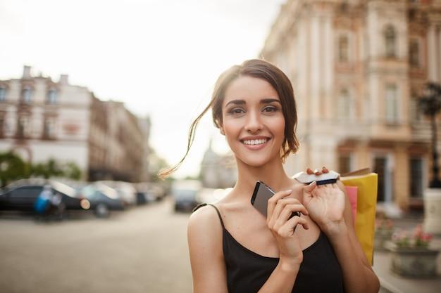 Sluit omhoog portret van jonge vrolijke knappe vrouw met donker haar in zwarte kleren met ontspannen glimlach