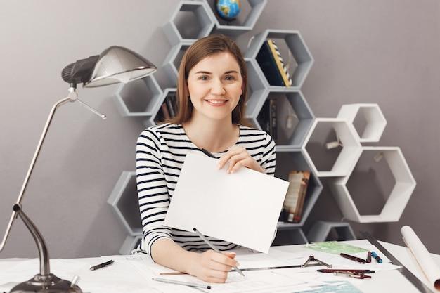Sluit omhoog portret van jonge vrolijke knappe vrouwelijke freelance architect met donker haar in het gestreepte overhemd glimlachen, die witboeklijst tonen, exemplaarruimte voor uw advertentie.