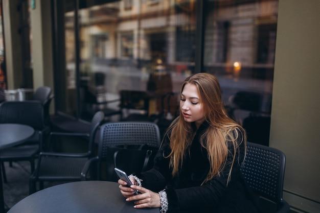Sluit omhoog portret van jonge vrouw freelancer met smartphone in handen