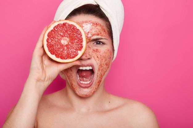 Sluit omhoog portret van jonge vrouw met boze gelaatsuitdrukking, schreeuwt in badkamers met witte handdoek op hoofd, bedriegt haar oog met grapefruit, heeft thuis schrobt op haar gezicht, kosmetische procedures.