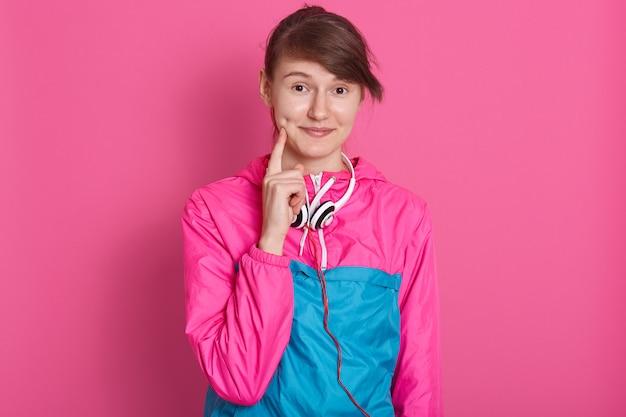 Sluit omhoog portret van jonge vrouw status glimlachend en houdend vingers op wangen terwijl het stellen