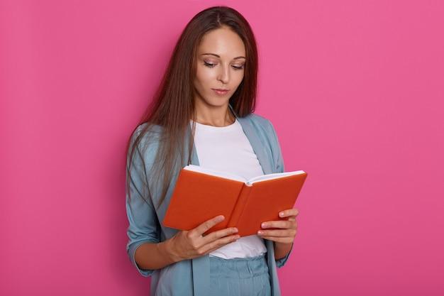 Sluit omhoog portret van jonge vrouwen die iets in notitieboekje lezen dat over rooskleurig wordt geïsoleerd