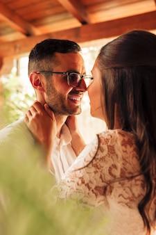 Sluit omhoog portret van jonggehuwdepaar die en op hun huwelijksdag strelen kussen. hou van concept.