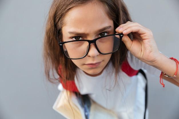 Sluit omhoog portret van kalm donkerbruin schoolmeisje in oogglazen