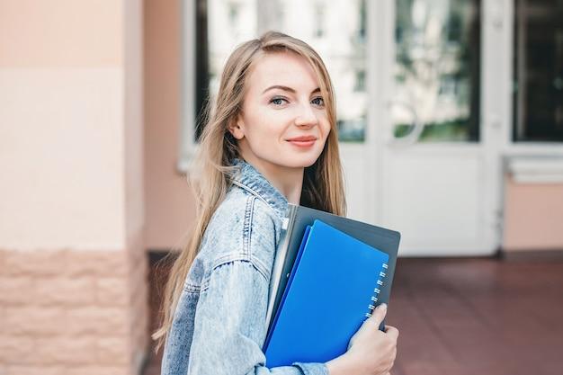 Sluit omhoog portret van kaukasisch vrouwelijk de holdingsnotitieboekje van het studentenmeisje, boek, omslag die zich voor universiteitsgebouw bevindt