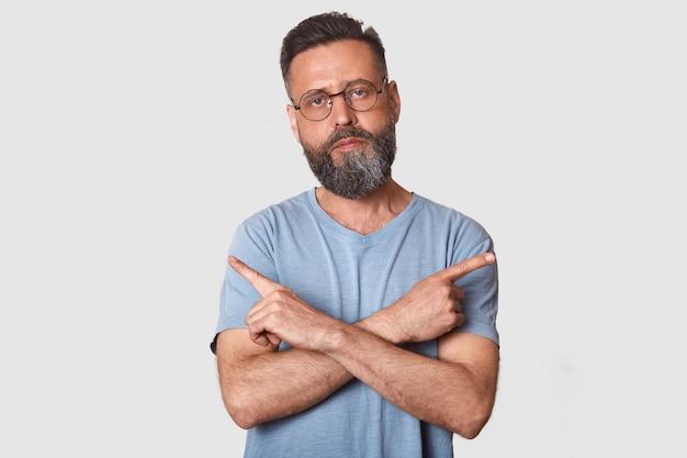 Sluit omhoog portret van kaukasische mannelijke punten aan verschillende kanten met wijsvingers, kan niet tussen twee punten kiezen, heeft kalme uitdrukking, die glazen en grijze t-shirt dragen, die over witte muur wordt geïsoleerd.