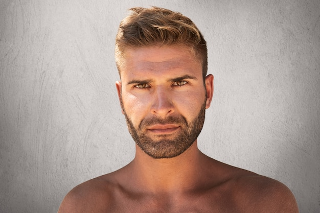 Sluit omhoog portret van knap mannetje met donkere ogen, varkenshaar en trendy kapsel dat naakt is