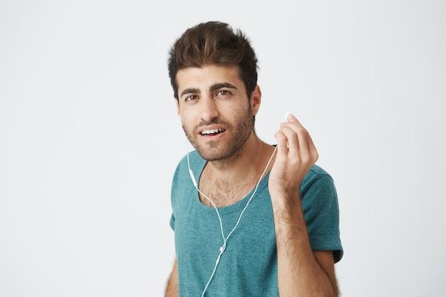 Sluit omhoog portret van knappe italiaanse kerel in trendy blauwe t-shirt. muziek luisteren en een hoofdtelefoon met de hand afzetten, in een poging te horen wat zijn vriend zei.