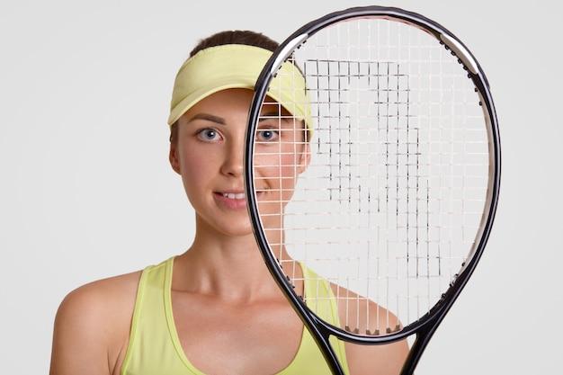 Sluit omhoog portret van knappe zelfbepaalde tennisspeler kijkt door racket, heeft gezonde schone huid
