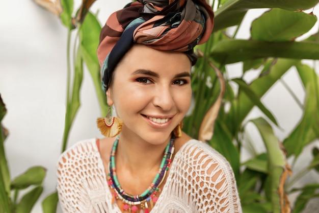 Sluit omhoog portret van lachende vrouw met een tulband bij het hoofd stellen over palmen
