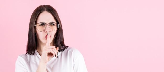 Sluit omhoog portret van leuke mooie aantrekkelijke vrouw die hush-gebaar maakt dat op roze exemplaar-ruimte als achtergrond wordt geïsoleerd