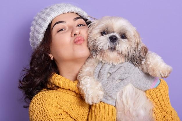 Sluit omhoog portret van meisje die gele gebreide modieuze uitrusting dragen die kusgebaar tonen, die met haar puppy stellen