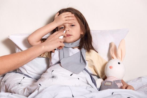 Sluit omhoog portret van moeder die de lopende neus van haar kind behandelen met neusnevel