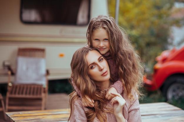 Sluit omhoog portret van moeder en weinig dochter die en in platteland op camper van vakantie koesteren ontspannen